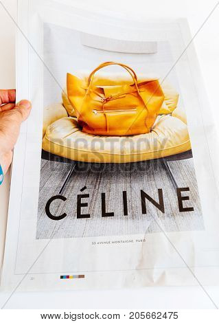 PARIS FRANCE - SEP 25 2017: Man reading international newspaper looking at Celine bag fashion advertising on the last page of French newspaper