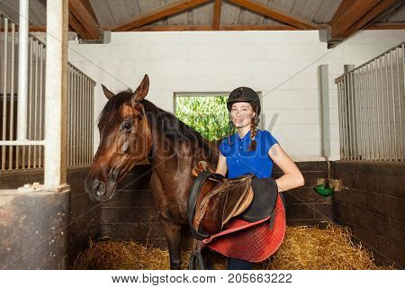 Beautiful jockey girl standing inside a box stall and holding saddle while preparing her purebred brown horse