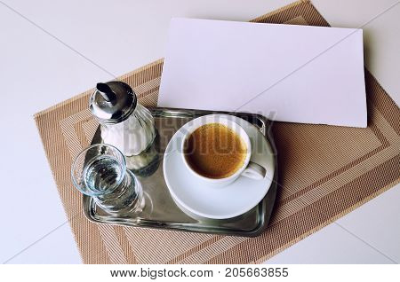 Serving coffee in the restaurant. Coffee a glass of water and sugar on an iron tray.