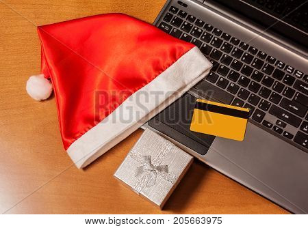 Christmas on line shopping concept. Credit card laptop gift box and santa hat top view on wooden background.