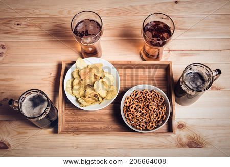 Beer mugs and glasses on wooden table. Beer snacks are chips and pretzels. Drink and snack for football match or party. Vintage style