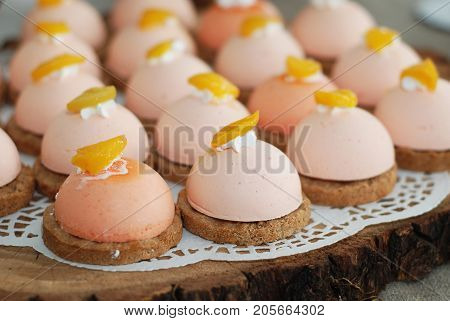 Mini strawberry mousse cakes decorated with fresh orange and cream. Candy bar.