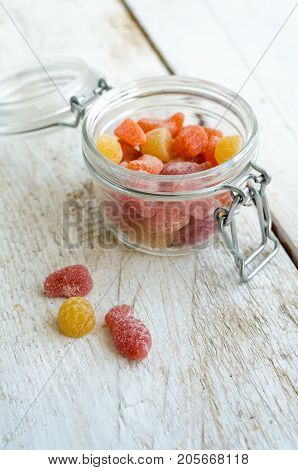 Vitamins gummy in the glass jar on white wooden background. Multivitamin candies in form of different kind of fruit. Nutrition supplement concept.
