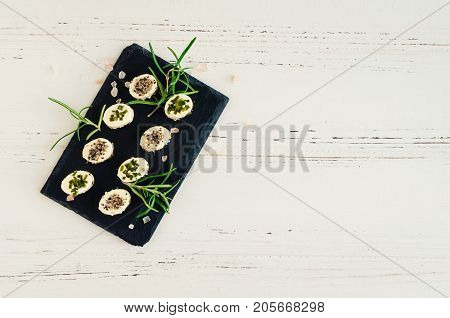 Mini appetizers bocconcini freschi from soft cheese with spices on dark stone board on white wooden background with place for text. Italian cuisine. Top view. Copy space.