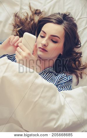 Hipster girl is reading text message from her boyfriend on mobile while is lying in the bed. Cheerful young woman in pajamas is watching video on cell phone before of after sleeping.