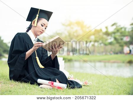 Graduate Reading Diary, Notebook In Her Hand Feeling Relaxing And So Happiness In Commencement Day