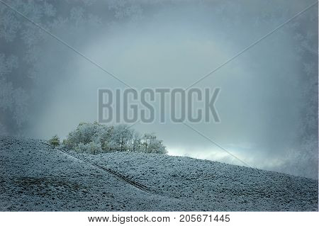 A snowy country hilltop in Wyoming with a vignette of ice crystals borders the image.