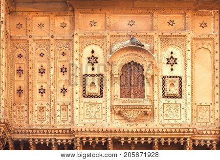 Closed window of an old house with carvings on walls. Indian tradition of architecture.