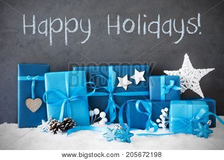 Concrete Wall With English Text Happy Holidays. Blue Christmas Gifts With Decoration Like Stars And Fir Cone On Snow.