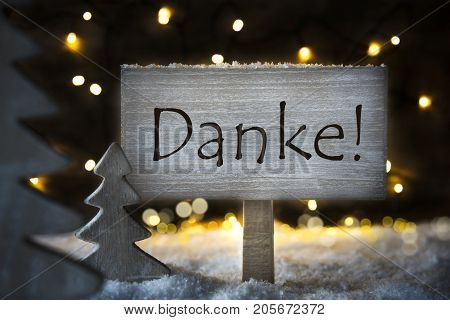 Sign With German Text Danke Means Thank You. White Christmas Tree With Snow And Magic Glowing Lights In Backround. Card For Seasons Greetings.