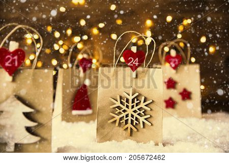 Christmas Shopping Bag With Numbers 21 to 24 On Snow. Decoration Like Santa Hat, Snowflake, Christmas Tree And Stars. Fairy Lights In Background And Instagram Filter. Snowy Scenery With Snowflakes