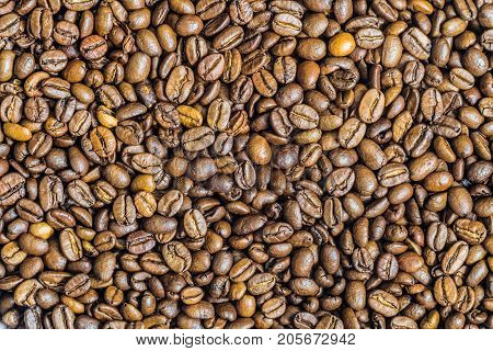 Roasted coffee beans background. Many coffee grains.