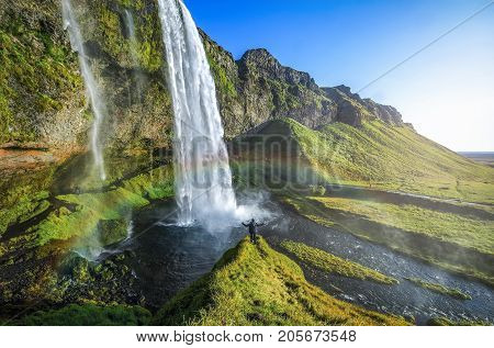 Tourist standing in front of Seljalandsfoss one of the best known waterfalls in southern Iceland The most famoust Icelandic waterfall beautiful amazing landscape from Iceland