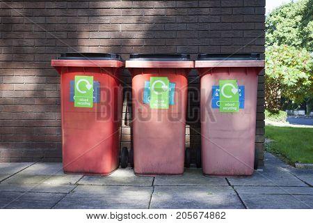 Three red garbage, trash bin eith writing mix recycling
