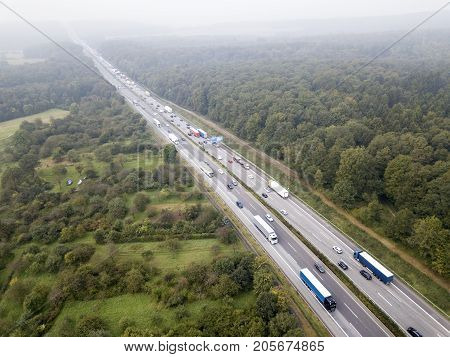 Aerial view of a highway in Germany. Traffic jam in one direction. Lots of trucks and small cars stuck in slow traffic
