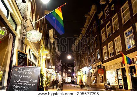 AMSTERDAM, NETHERLANDS - 12rd of MARCH 2012: Beautiful little traditional houses and bar with LGBT symbol in Amsterdam by night. March 12th, 2012. Amsterdam, Netherlands.