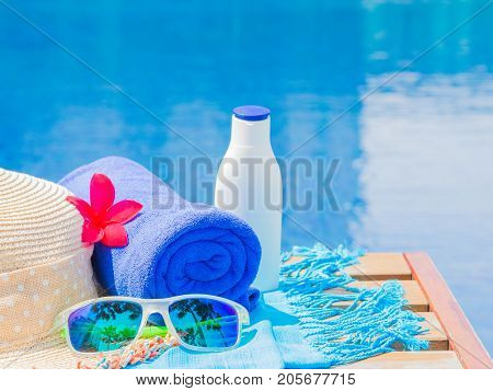 Sunglasses beach hat blue towel and sunscreen at the side of swimming pool. Vacation beach summer travel concept
