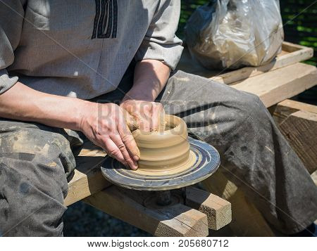 Mens hand made pottery clay old-fashioned way. The concept of the production of pottery in the past.