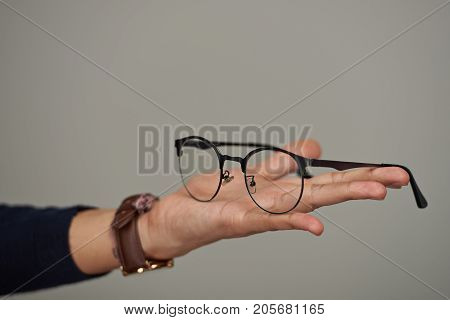 Eyeglasses lay on human palm isolated on gray background