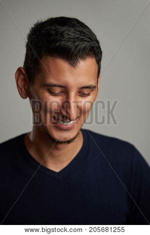 Happy shy young hispanic man smiling and look down