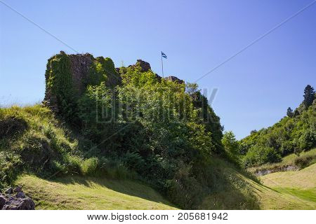 A section of the Urquhart Castle Ruins brightly illuminated by the sun with the Scottish Flag flying in the breeze.
