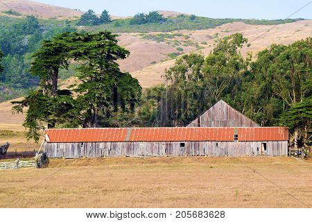 Forgotten landscape including a haunting image of a collapsing wooden barn taken at the rural Northern California Coast in Sonoma County, CA