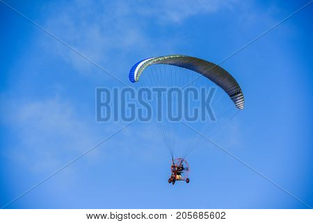 Un-identified man flying with glider in the clear sky day