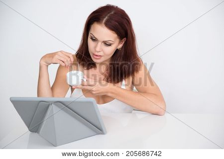 Portrait of serious young Caucasian woman sitting at touchpad and drinking coffee