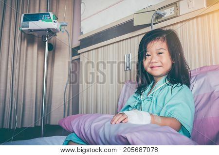 Illness Asian Child Admitted In Hospital With Saline Intravenous On Hand.