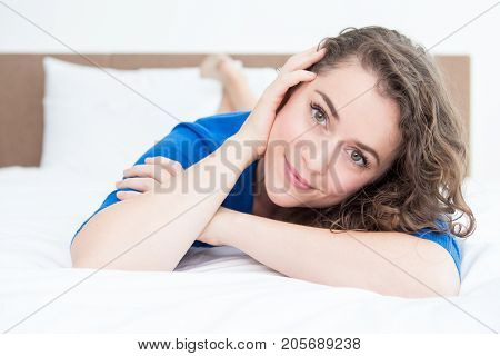 Closeup portrait of smiling young beautiful woman looking at camera and lying on bed in bedroom. Front view.