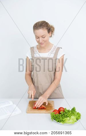 Careful mother using recipe book while cooking dinner for family. Smiling pretty young woman cutting vegetable on board. Healthy food concept