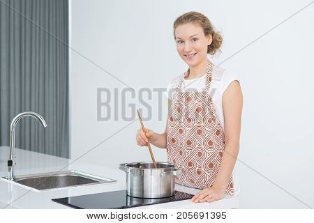 Cheerful attractive housewife stirring soup with wooden spoon in cooking pot on electric cooker and smiling at camera. Pretty mother cooking dinner. Housework concept