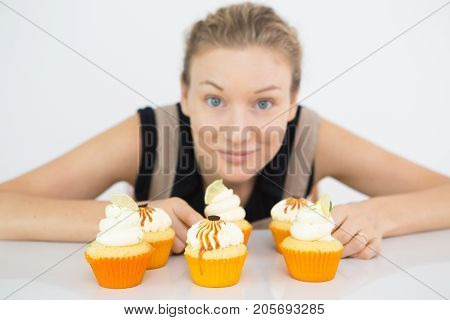 Pretty young woman cooking appetizing custom-made cupcakes. Six Halloween cupcakes decorated with cream placed on table. Small business concept