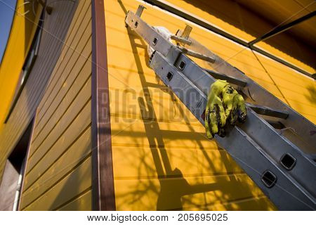 Yellow rubber gloves laid on the telescopic ladder next to the fresh painted wall of a wooden house