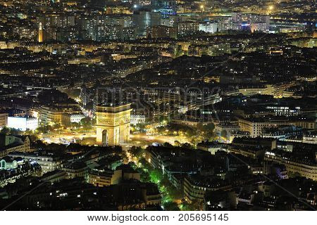 Aerial Night view of Arc de Triomphe and Paris City shot on the top of Eiffel Tower