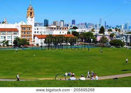 September 19, 2017 in San Francisco, CA:  People relaxing on a lawn overlooking the San Francisco Skyline taken at Dolores Park where people can relax and enjoy recreational activities while enjoying views of the city taken in San Francisco, CA