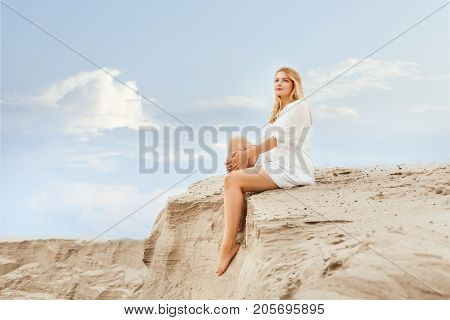 Woman sits on the dunes and dreams of staring into the distance.