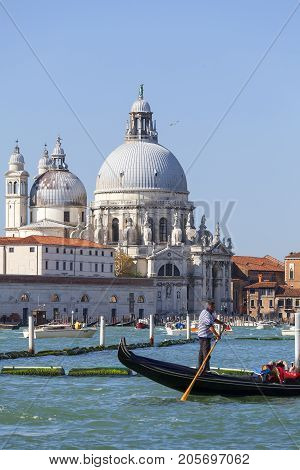 VENICE ITALY - SEPTEMBER 21 2017: Baroque church Santa Maria della Salute sea view with gondolier. It was built in the 17th century as a votive thanksgiving after the plague epidemic