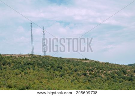 Two Communication towers on the top of the mountain with sky background