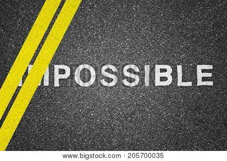 Word impossible is over asphalt texture background