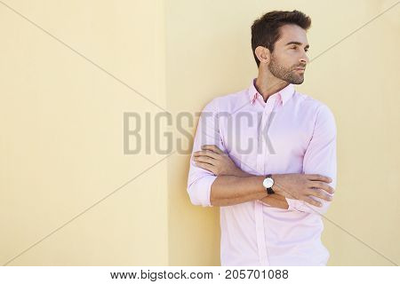 Guy in pink shirt on yellow wall looking away