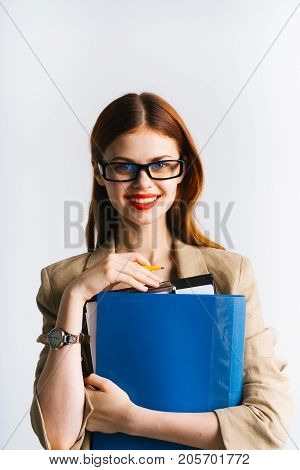 Fashionable young business woman with documents looking into the camera and smiling