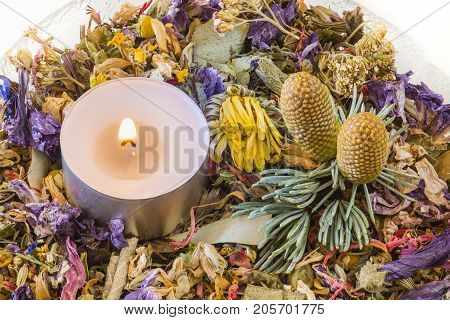 Glass bowl with potpourri of dried flowers candle and two pinecones.