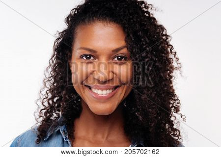 Charming smile. The close up of a beautiful curly young woman in a denim shirt posing on a white background and smiling at the camera