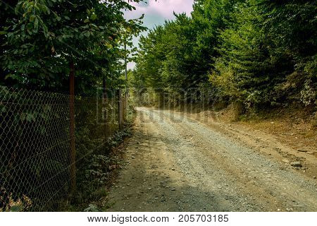 Gravel land road to a farm with wiring fence