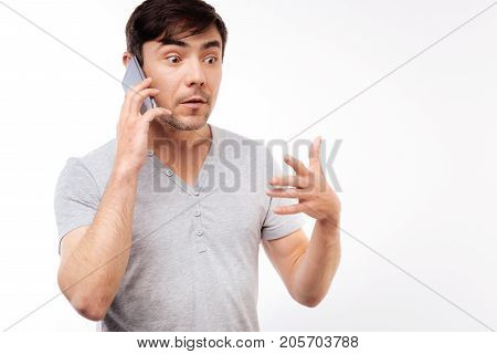 Baffled by news. Handsome young man talking on the phone and having a surprised facial expression as if being shocked by news