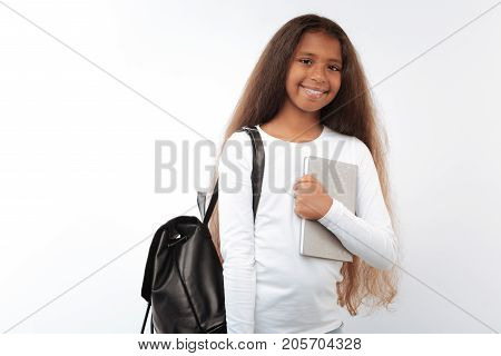 Happy schoolchild. Pretty pre-teen girl posing on a white background, wearing backpack and pressing notebook to her chest