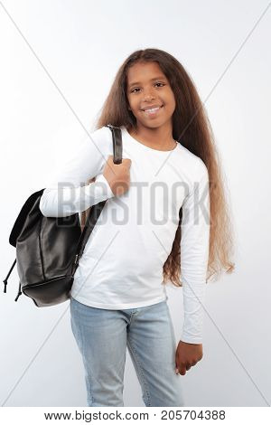 Cheerful schoolkid. Pleasant pre-teen girl posing on a white background while wearing a black backpack on her shoulder and smiling at the camera