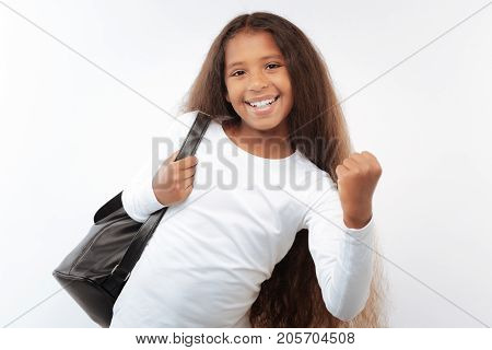 Reaching goals. Adorable pre-teen girl with a swarthy complexion and a long auburn hair posing on a white background while wearing a black backpack and making a yes gesture