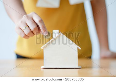 Asian woman putting money coin in to house piggy bank metaphor saving money financial for buy the home shallow depth of field select focus on house